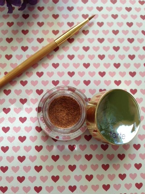 closeup of Tarte Clay Pot Cream Eyeliner, bronze metallic Spirit Animal with Etch & Sketch eyeliner brush in the background neversaydiebeauty.com