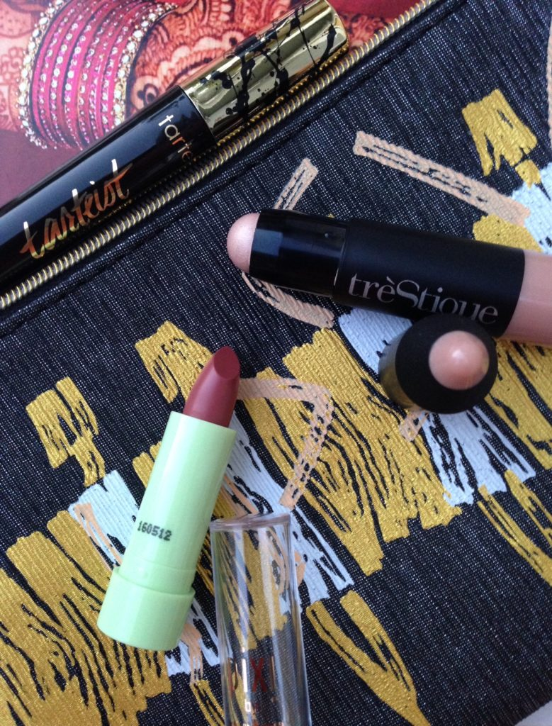 ipsy Glamazon bag, closeup of Tarteist, Pixi Lipstick Rose Eternelle and TreStique Maldives Luminiscent Stick neversaydiebeauty.com