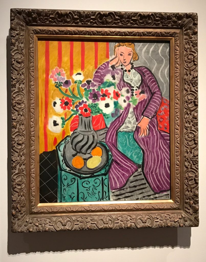 Matisse painting of a woman with a vase of flowers on a table