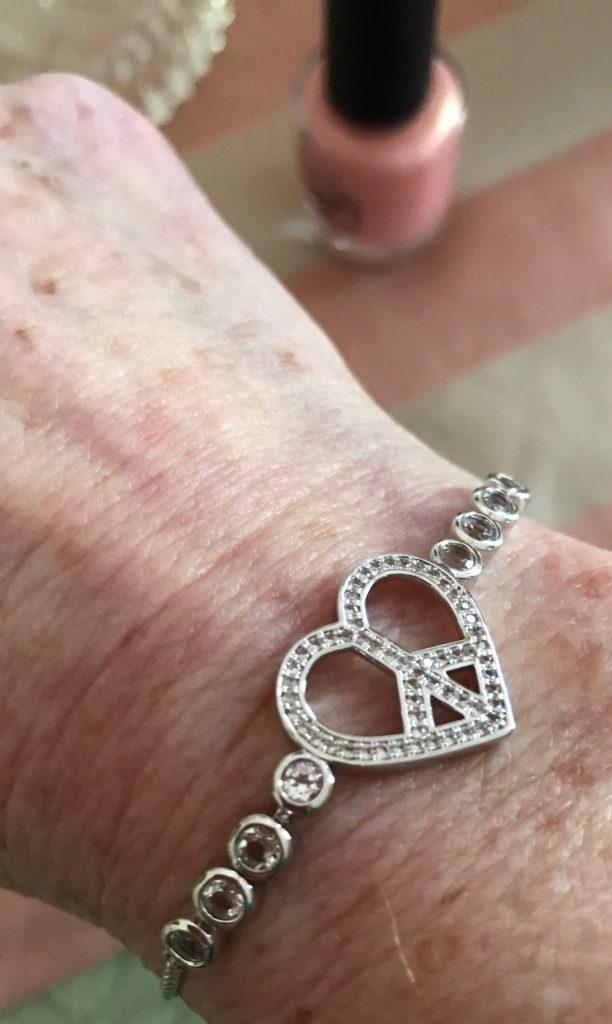 closeup of heart-shaped peace sign in white topaz in silver tone slide bracelet, neversaydiebeauty.com