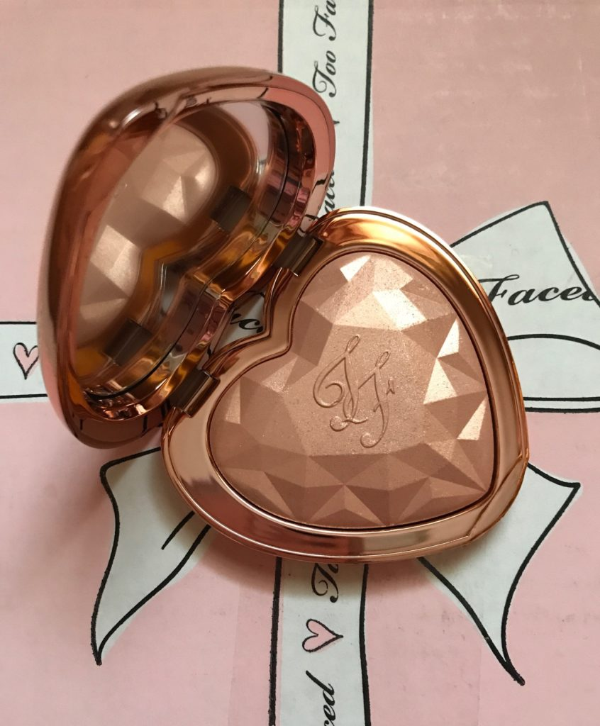 Too Faced Love Light Highlighter open compact, shade Ray of Light rose gold pressed powder embossed with TF initials and prismatic shape, neversaydiebeauty.com