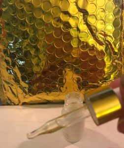 glass dropper filled with Shine Brightening Oil, neversaydiebeauty.com