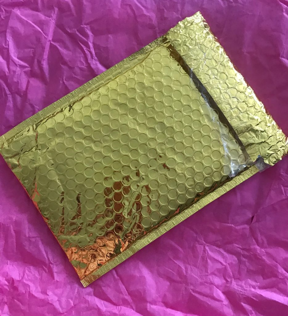 gold metallic mailing envelope from Ipsy, neversaydiebeauty.com