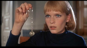 Mia Farrow in Rosemary's Baby holding the tannis root necklace, neversaydiebeauty.com