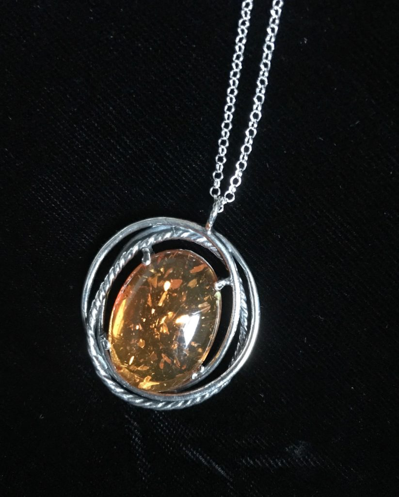 closeup of amber pendant with Sterling Silver from Uno Alla Volta, neversaydiebeauty.com