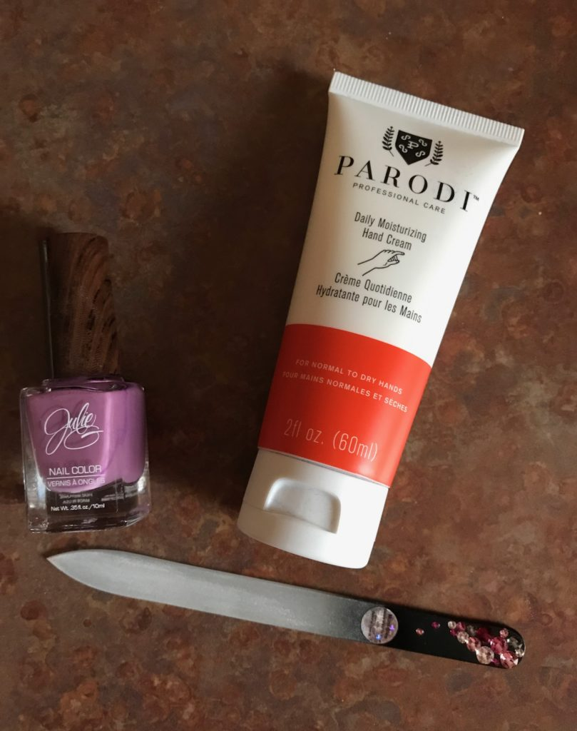 Parodi Daily Moisturizing Hand Cream tube with nail polish and glass file flatlay, neversaydiebeauty.com