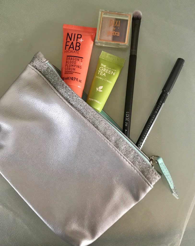 cosmetics spilling out of Ipsy Snow Globe silvery makeup bag, neversaydiebeauty.com