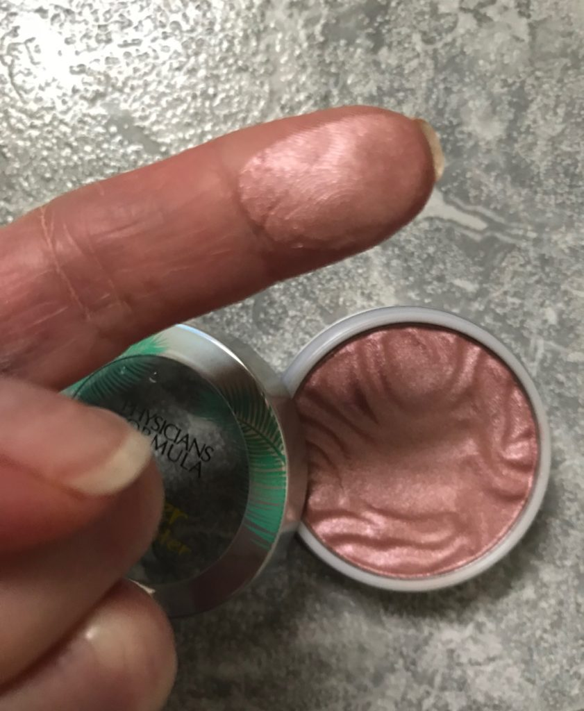 finger swatch of the pink Physicians Formula Butter Highlighter, neversaydiebeauty.com