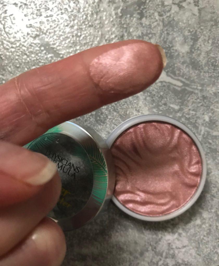 finger swatch of the pink Physicians Formula Butter Highlighter, neversaydiebeauty.com