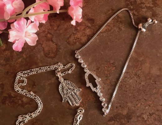 silver necklace and bracelet with the hamsa symbol as centerpiece, neversaydiebeauty.com