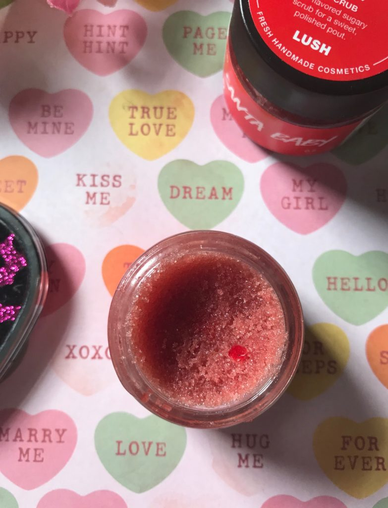 open LUSH Santa Baby Lip Scrub showing a tiny red edible heart in the scrub, neversaydiebeauty.com